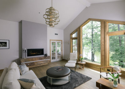 Fireplace on marble hearth in living room. Large window with view of lake.