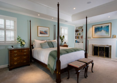 Bedroom with four-post bed and light blue walls plus traditional period mantle and fireplace