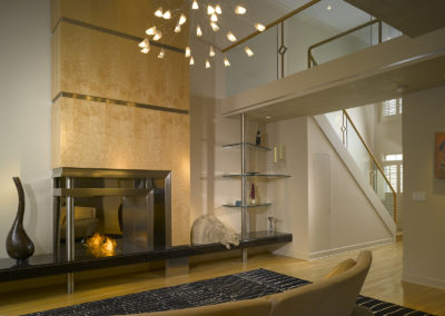 Contemporary living room with ethanol burning fireplace, bird's eye maple face and stainless steel inserts on black granite hearth, plus artistic chandelier and glass pane railing
