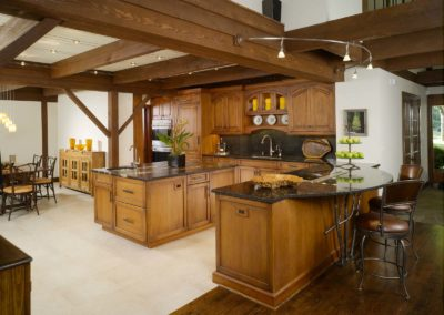 View of contemporary Lodge kitchen with white linoleum floors and black granite countertops on wooden counters