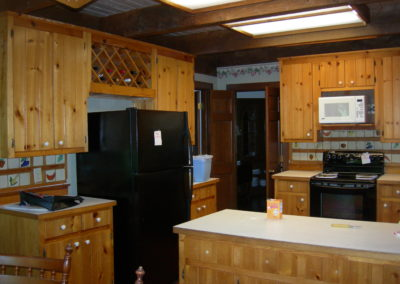 Rustic kitchen before renovation showing outdated cabinetry and appliances